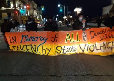 An image of an orange and yellow banner held up by five protestors. The banner says,
