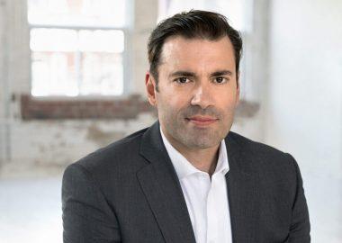 Monsieur Marc-Antoine Desjardins vêtu d'une veste noire sur chemise blanche, assis sur une chaise.