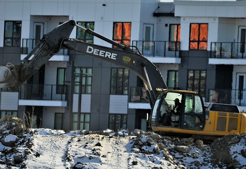 A construction truck digging in front of a townhouse complex.