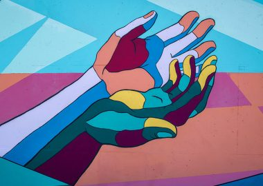 An image of a painting depicting outstretched hands. They are cupped and painted in blue, orange red, yellow, green and brown.