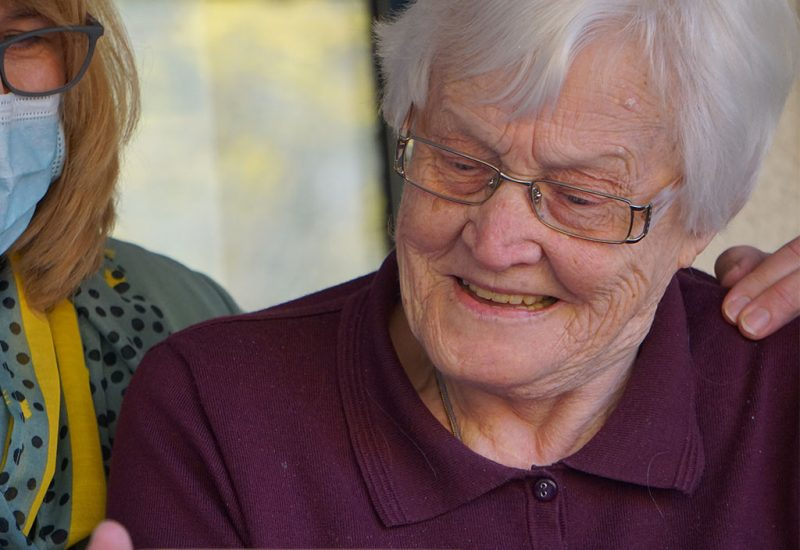 An image of an elderly woman smiling while looking at something on a phone screen.