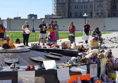 An image of Jackie Shigwadjah in a ribbon skirt holding a bullhorn. Behind her is a line of drummers and in front of here is a temporary memorial to the Kamloops 215.