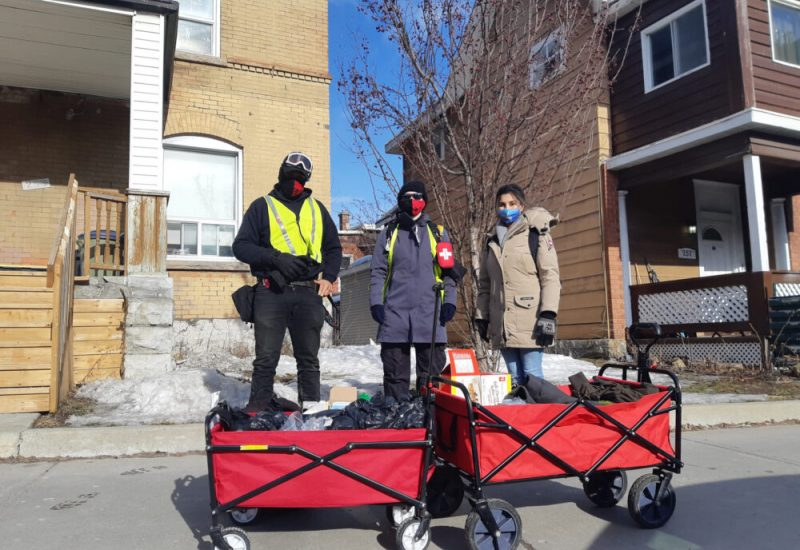 Three people wearing masks, two wearing high visibility vests, standing behind two red wagons. These wagons are filled with supplies for the homeless.