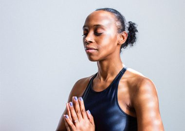 A Black woman meditates with her eyes closed and her hands pressed together at heart centre against a grey background