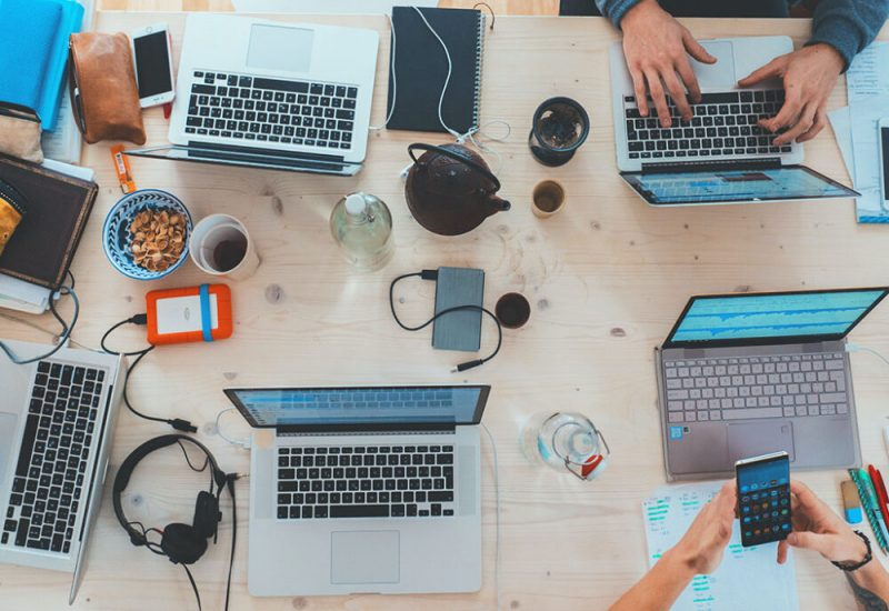An overhead image of a desk with multiple devices on it. Hands are seen typing and there are cups of coffee, and cables strewn across the table.