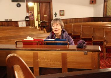 Woman sings and plays piano in an empty church