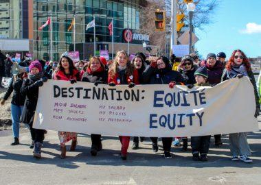 Groupe de gens qui marchent ensemble dehors au Centre Avenir avec une affiche qui lit: DESTINATION: mon salaire, mes droits, mon autonomie ÉQUITÉ / my salary, my rights, my autonomy EQUITY