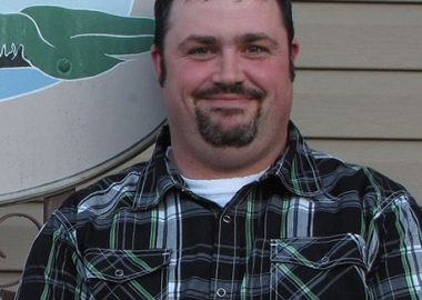 A headshot of Maurice Beauregard in front of a building wearing a plaid shirt.