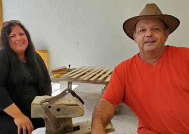 A woman and man sit in a workshop in front of a table where a canoe is being built