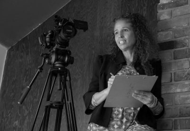 A black and white photo of Mia Golden holding a clipboard behind a camera