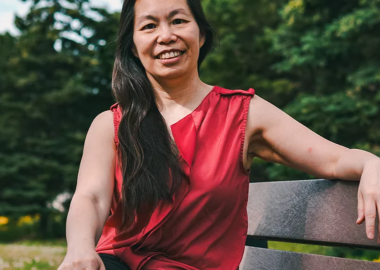 A woman in a red shirt sitting on a bench outside.