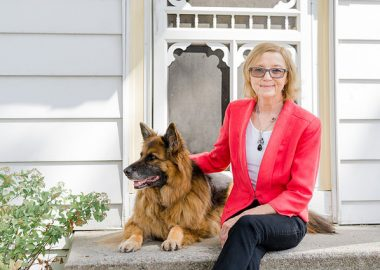 Michelle Nadon sitting on the porch with her German Sheppard