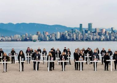 A group of family members stand with white crosses in front of them on a beach in Vancouver on a cloudy day