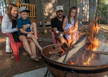 Une famille assise devant un feu à côté d'un chalet en forêt