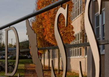 Photo of a metal sign reading NDSS with an image of Vancouver Island in front of a school on a fall day.