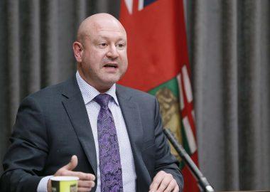 Dr. Brent Roussin en conférence de presse devant un drapeau du Manitoba
