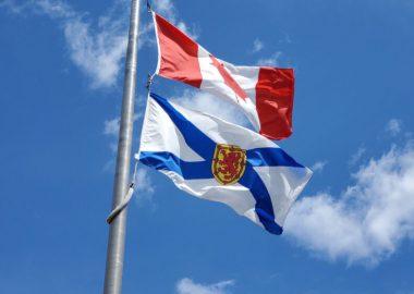 Nova Scotia and Canada flags flying on a flag pole against a blue sky