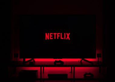 Un écran de télévision affichant le logo de Netflix en rouge sur un écran noir dans une pièce sombre lègèrement éclairé en rouge