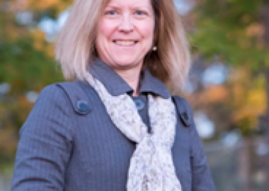 A shot of Nicole Thompson standing in front of trees in autumn wearing a grey coat and a white scarf.