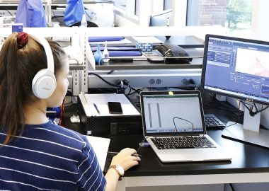 Student with headphones sits at computer screens and operates a mouse.