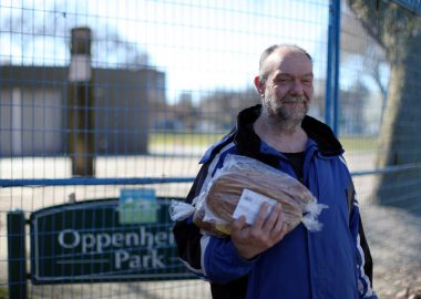 Downtown Eastside resident Paul Young holds loaves of bread outside with a green Oppenheimer Park sign behind him