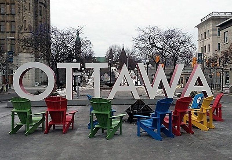 Des chaises multicolores entourent l'enseigne d'Ottawa située sur la rue York. Photo: heritagedowntowns.com