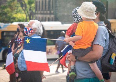 Un père porte ses enfants, ils tiennent un drapeau acadien, au fond il y a des personnes habillés aux couleurs de l'Abadie et un bus d'Halifax Transit