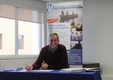 Assis à son bureau, le président du Collège Aurora, Andy Bevan.