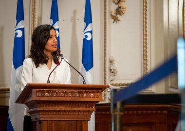 Dominique Anglade derrière un lutrin en bois, portant une blouse blanche et entouré de drapeaux du Québec
