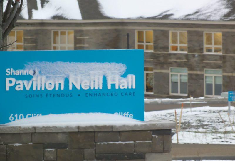 Un panneau enneigé sur lequel il est écrit : Pavillon Neill Hall, en arrière-plan le pavillon