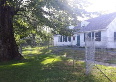 A photo of the construction fence around Perkins House.