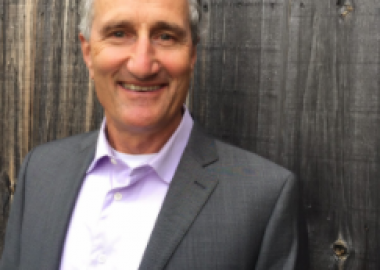 A man in a grey suit against a wooden background outside.