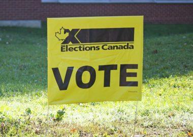Pancarte jaune sur laquelle est écrit le mot VOTE en grosses lettres noires
