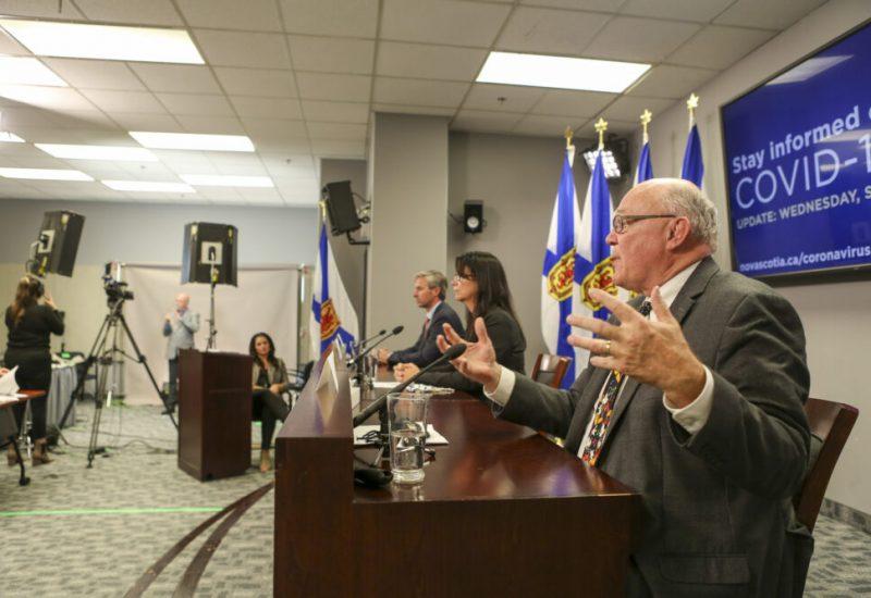 Deux hommes et une femme , assis devant des micros, répondent aux questions des journalistes dans une salle avec drapeaux de la Nouvelle-Écosse.