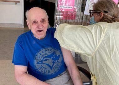 Une infirmière en blouse jaune vaccine un homme âgé en chemise bleue, le monsieur porte un pantalon kaki sur lequel , il a posé sa main , nous pouvons apercevoir que le monsieur porte des vernis rouges aux doigts.
