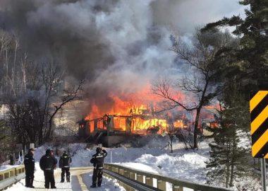 L'édifice du Black River INN en feu avec des pompiers en uniformes ainsi que des policiers