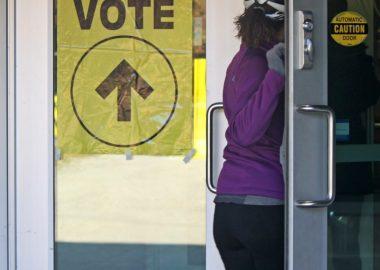 Une électrice suit la consigne d'une affiche jaune d'Élections Canada lui indiquant l'endroit du vote.