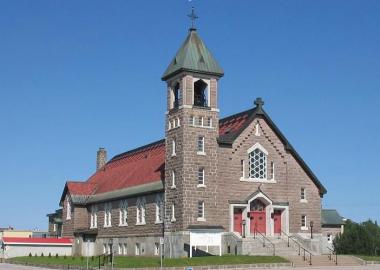 Grande église de couleur grise avec toiture et porte rouge. Fond de ciel bleu sans nuage.