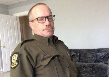 Un policier en uniforme de la SQ prend la pose, bien calme, dans une pièce éclairée.
