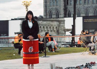Dame à gauche, cheveux noirs, chemise blanche, veston noir, jupe orange avec logo autochtone. Elle a des souliers noirs derrière plusieurs souliers d'enfants. En arrière plan, il y a une terasse avec des gens assis et l'édifice parlementaire d'Ottawa.