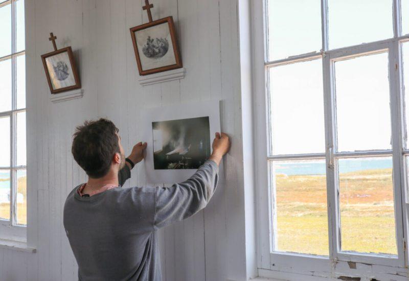 Un photographe vu de dos recadre une photo de son exposition, à côté d'une fenêtre