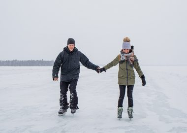 Two people skating on a frozen lake in a snow storm