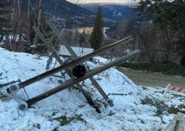 A powerline down on snow with Kootenay Lake in the background.