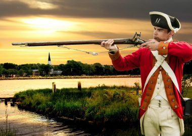 A photo of a privateer with a long gun standing against a backdrop of Nova Scotia at sunset.