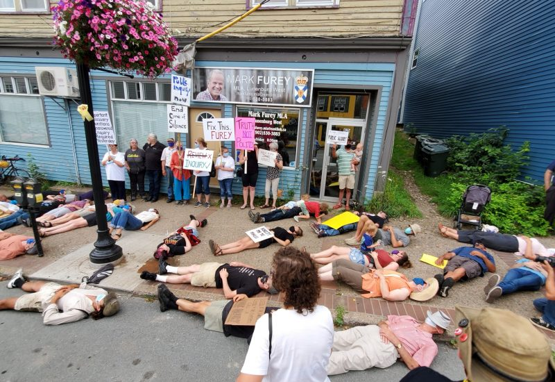 Protesters calling for a public inquiry into the April mass shooting lie on the sidewalk in front of Justice Minister Mark Furey's office to represent the 22 people killed