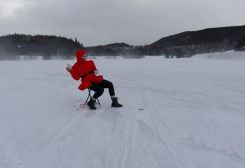 The Queer Mummer sits in winter clothing on a folding chair on a frozen body of water.
