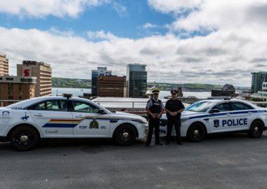 Une voiture de la GRC fait face à une voiture de la police d'Halifax. Les deux officier pose devant leur véhicule. Ils sont devant un paysage d'Halifax, on voit les building et le port au fond.