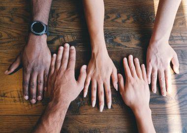 Des mains de couleurs différentes posées sur une table