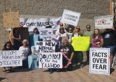 Plusieurs manifestants à l'extérieur avec des pancartes à la main.