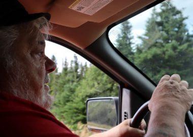 Le maire et préfet Randy Jones est photographié à bord de sa camionnette. Il porte un t-shirt rouge. En arrière-plan, on voit la forêt.